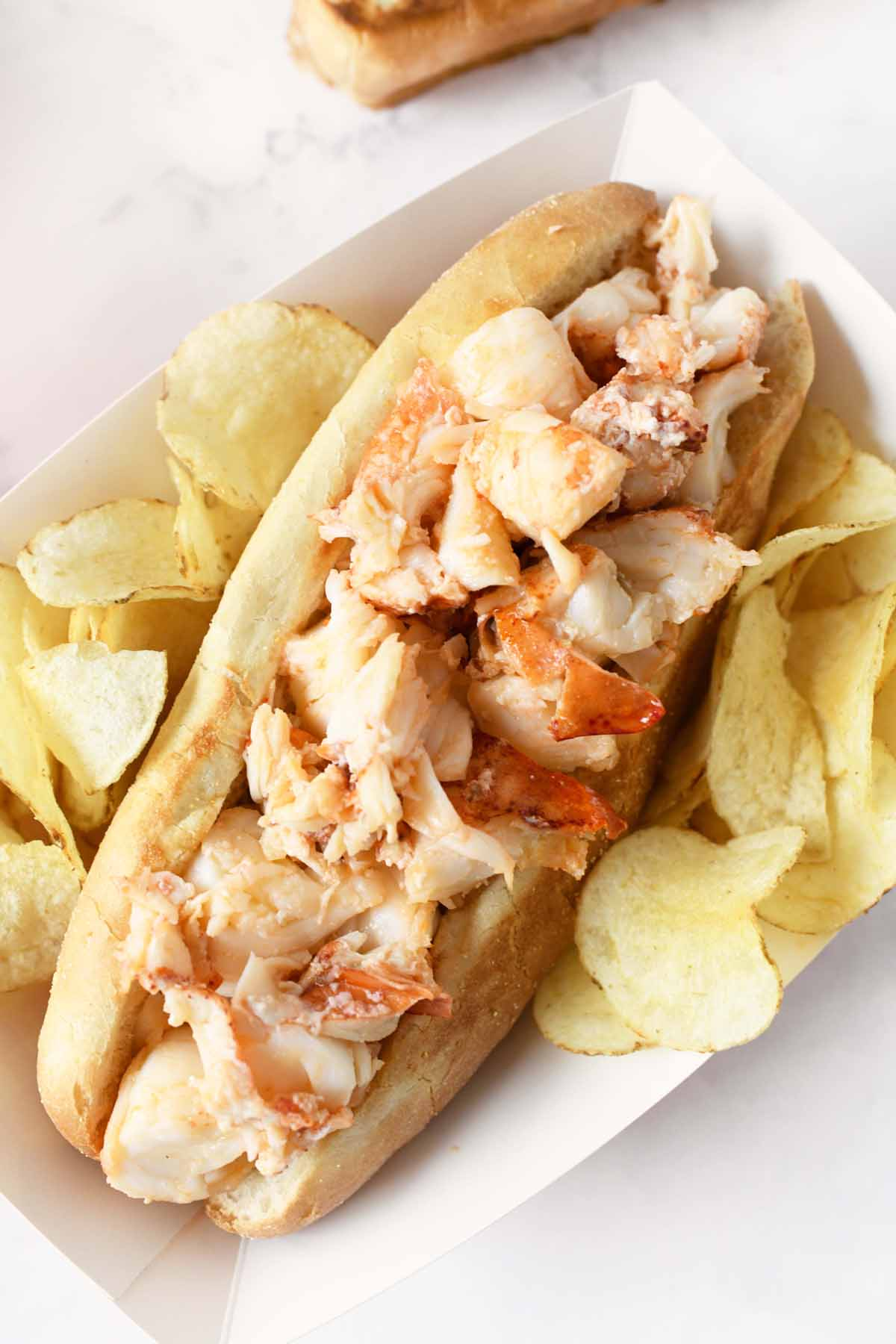 Buttered Lobster Roll in a paper plate with potato chips.