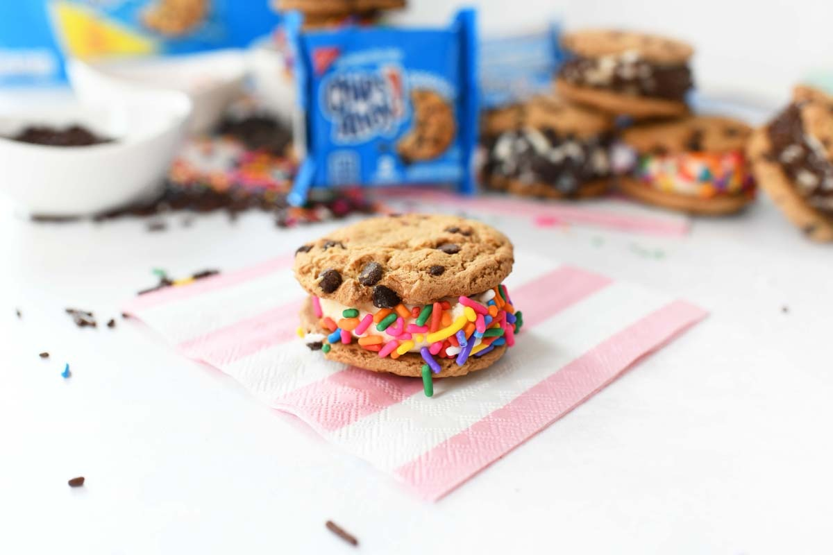 Mini rainbow sprinkle Chips Ahoy! cookie on a pink striped napkin.