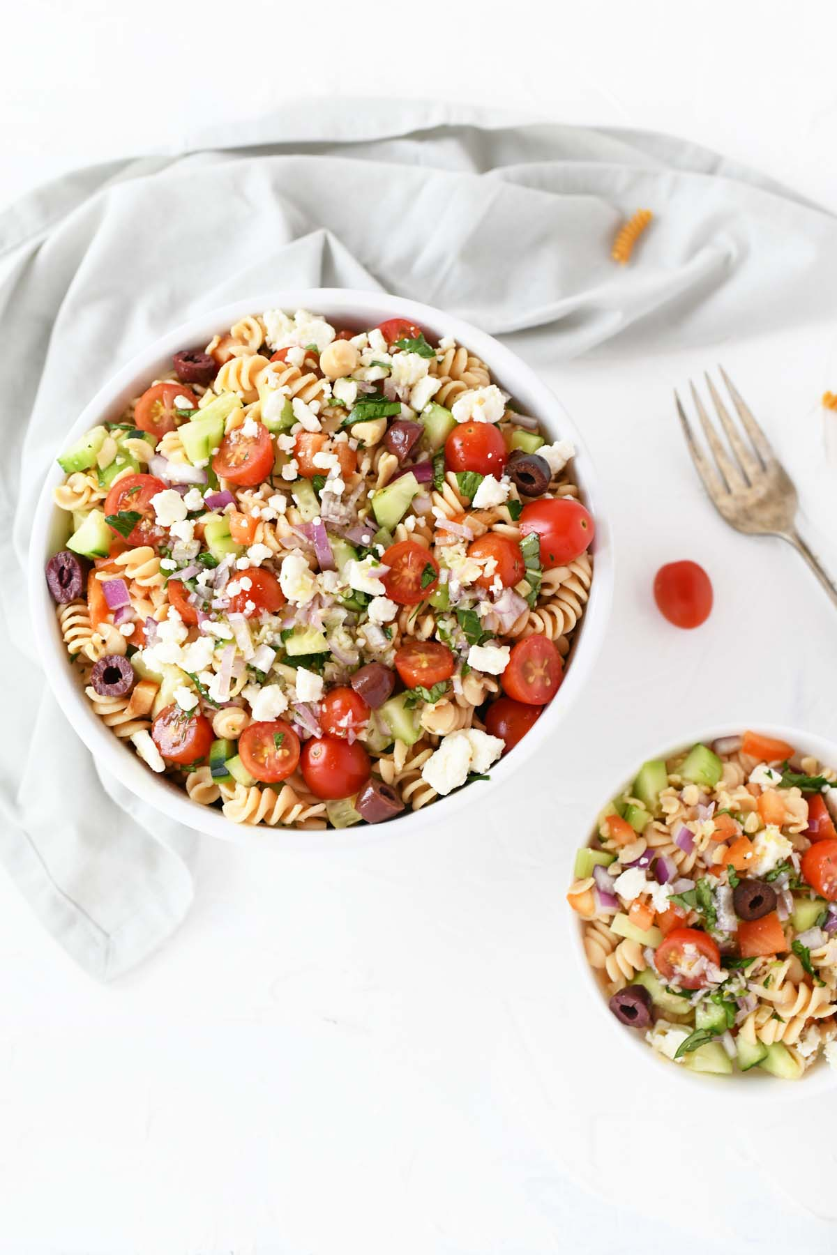 Colorful Greek Pasta Salad in a large and small bowl with a fork.