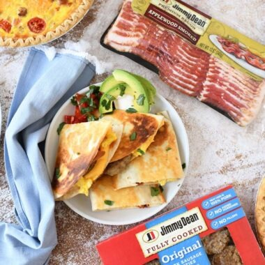 A colorful brunch of quesadillas, egg, sausage, and bacon on a table.