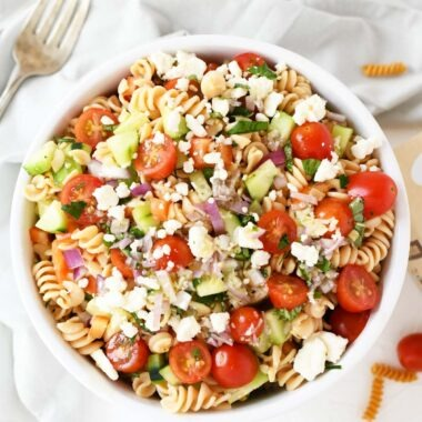 A colorful bowl of Greek salad with feta cheese in a white bowl.