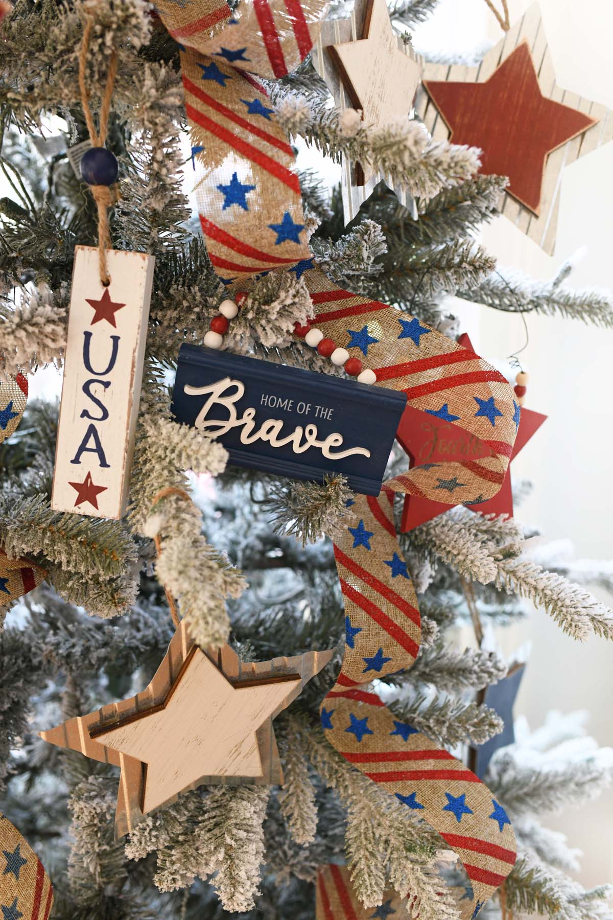 Red, white, and blue rustic ornaments on a tree.