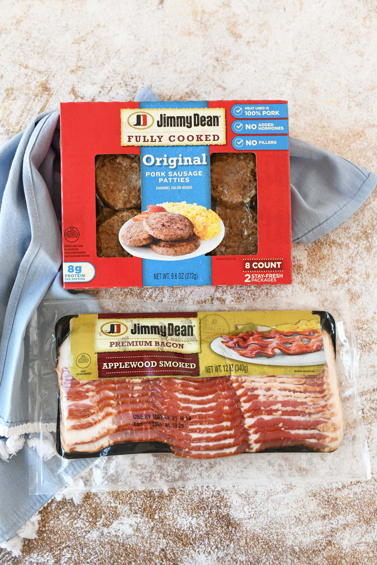 Jimmy Dean Bacon and Sausage packages on a wooden table with a blue napkin.