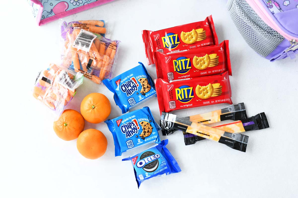 Oranges, carrots, RITZ crackers, and cookie packs on a white table.