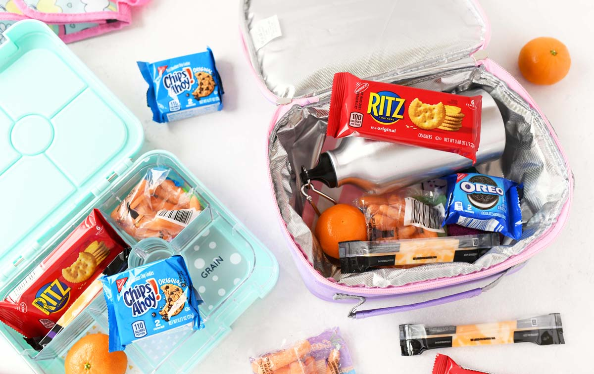 Kids lunchboxes filled with snacks like RITZ, Chips Ahoy! and mini oranges.