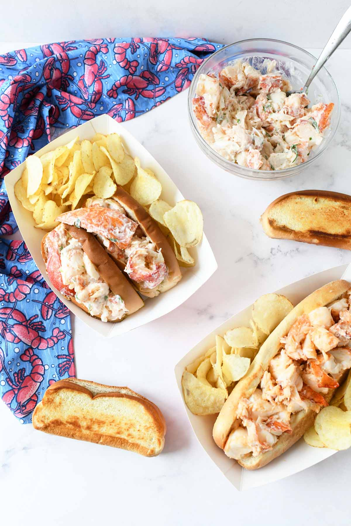 Lobster Rolls in paper containers with potato chips and a lobster napkin.