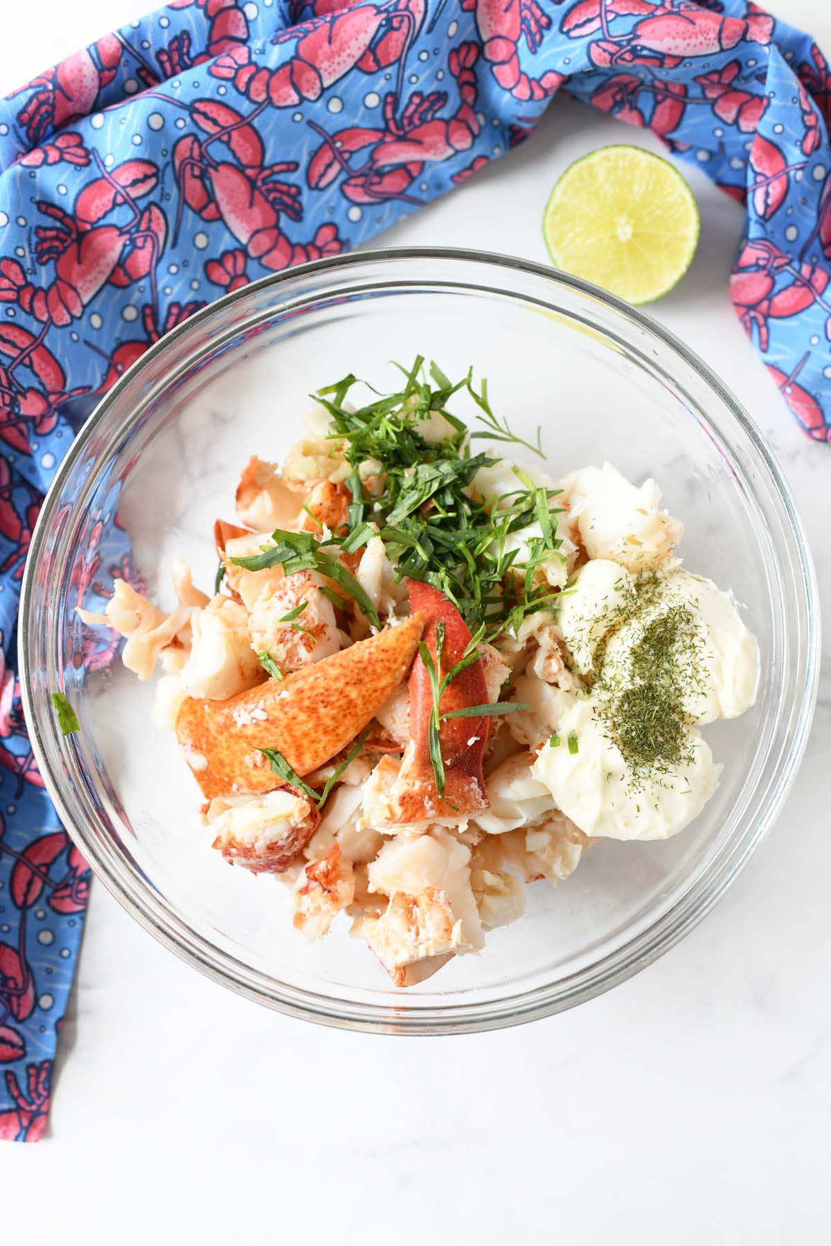 Lobster, mayo, green herbs, and lime in a glass bowl with a lobster napkin.