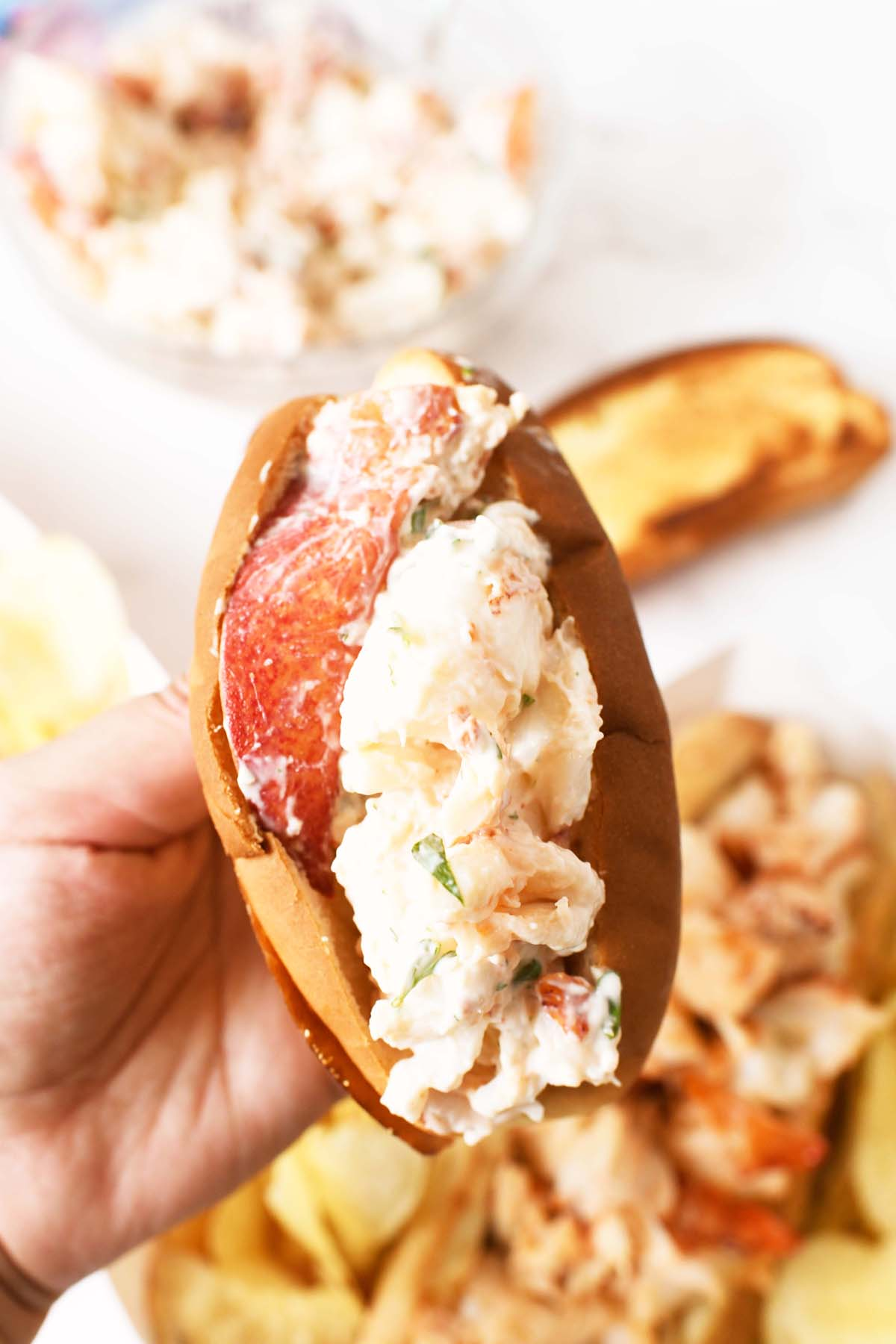 Lobster salad stuffed in a toasted min hot dog bun in a hand.