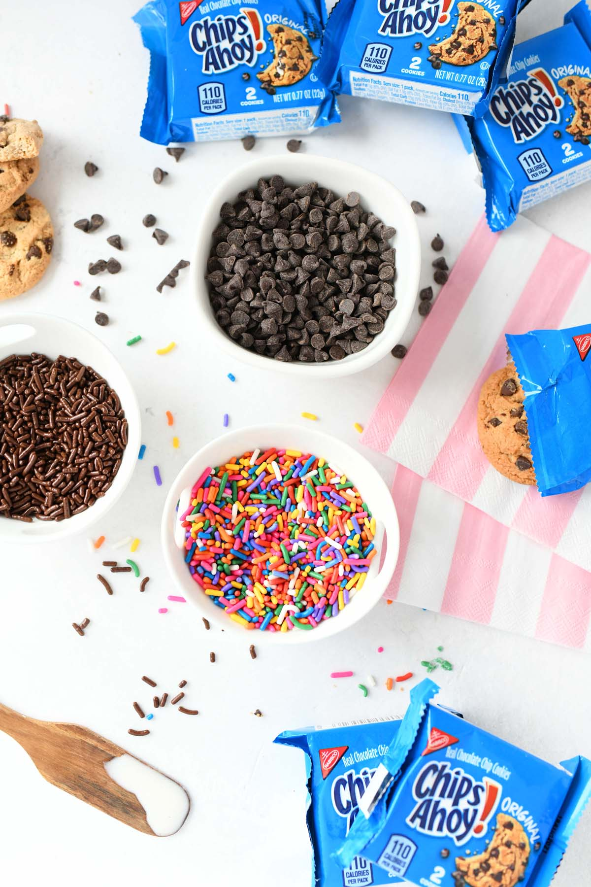 Sprinkles, mini chocolate chips, and Chip Ahoy! packs on a white table.