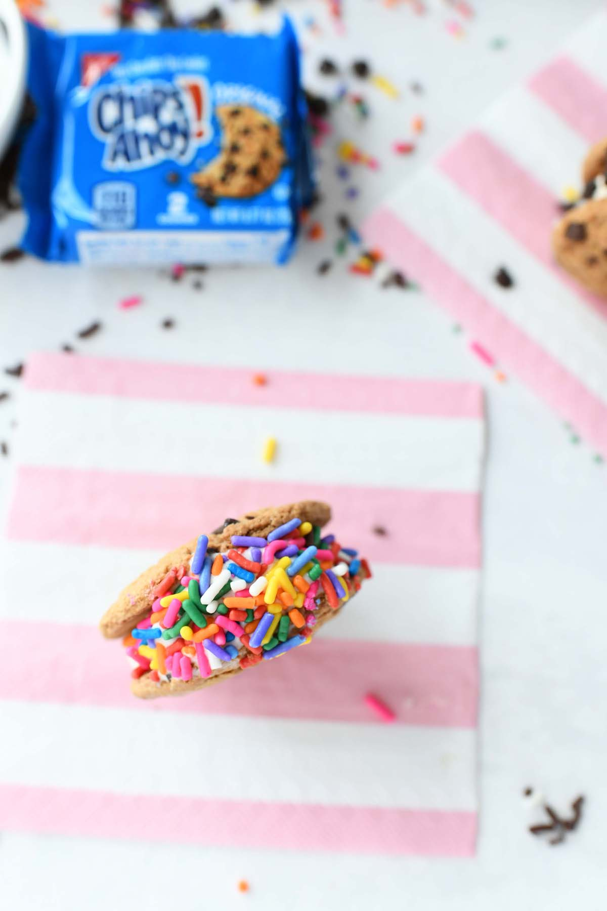 Rainbow Ice Cream Sprinkles Cookiewich on a pink striped napkin.