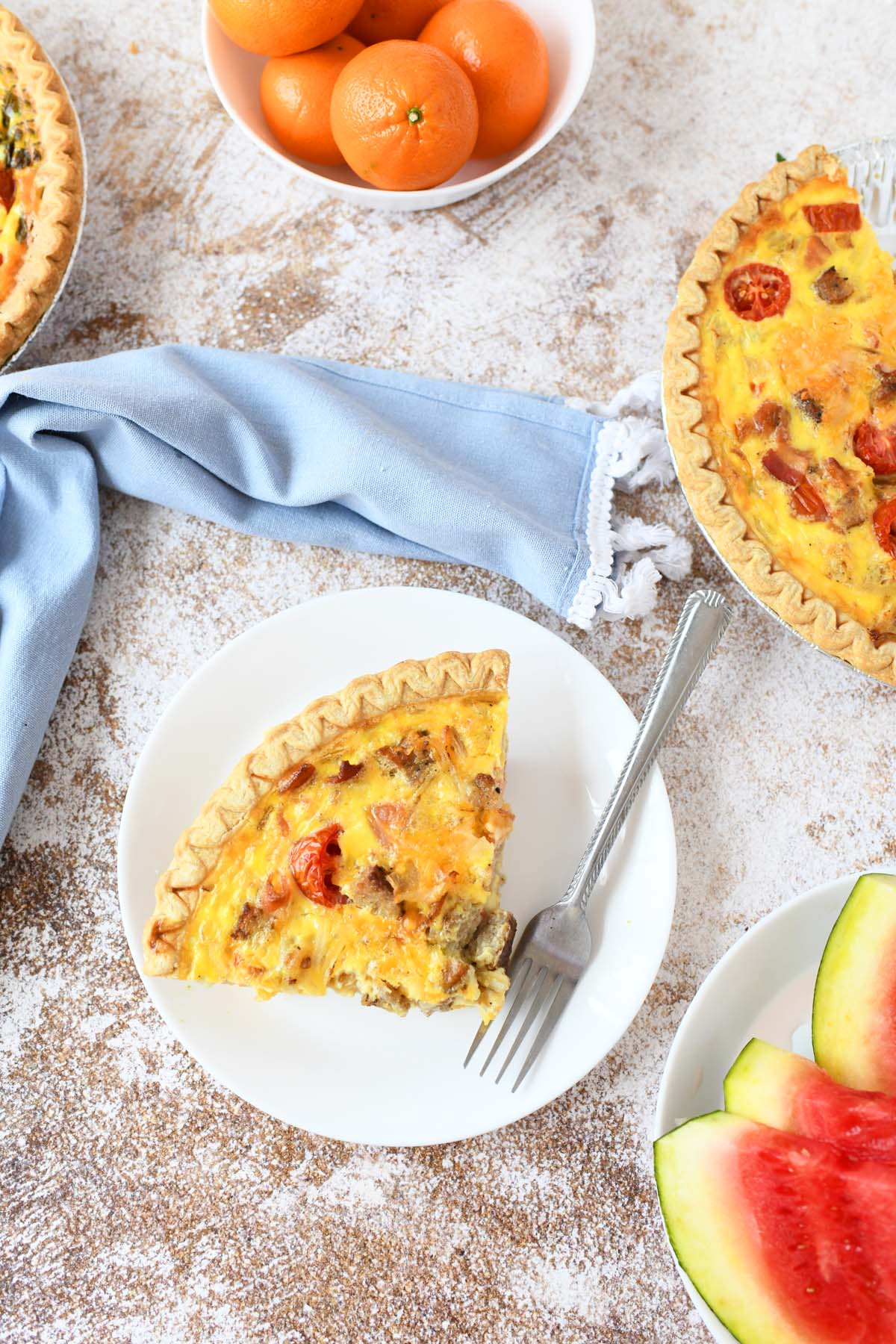 Slice of breakfast quiche on a white plate with fresh fruit around.