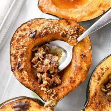 A silver spoon tucked inside a pecan filled acorn squash.