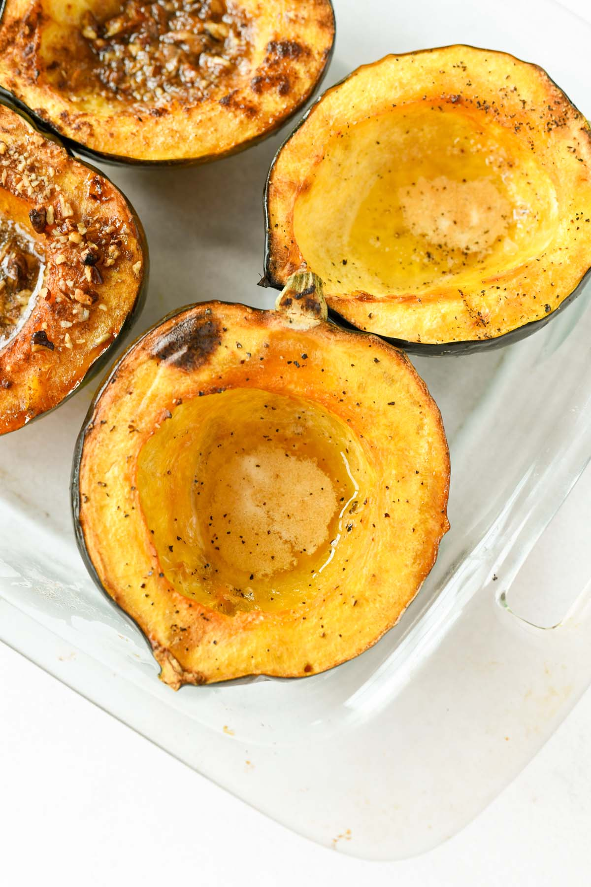 Honey buttered acorn squash in a clear glass baking dish.