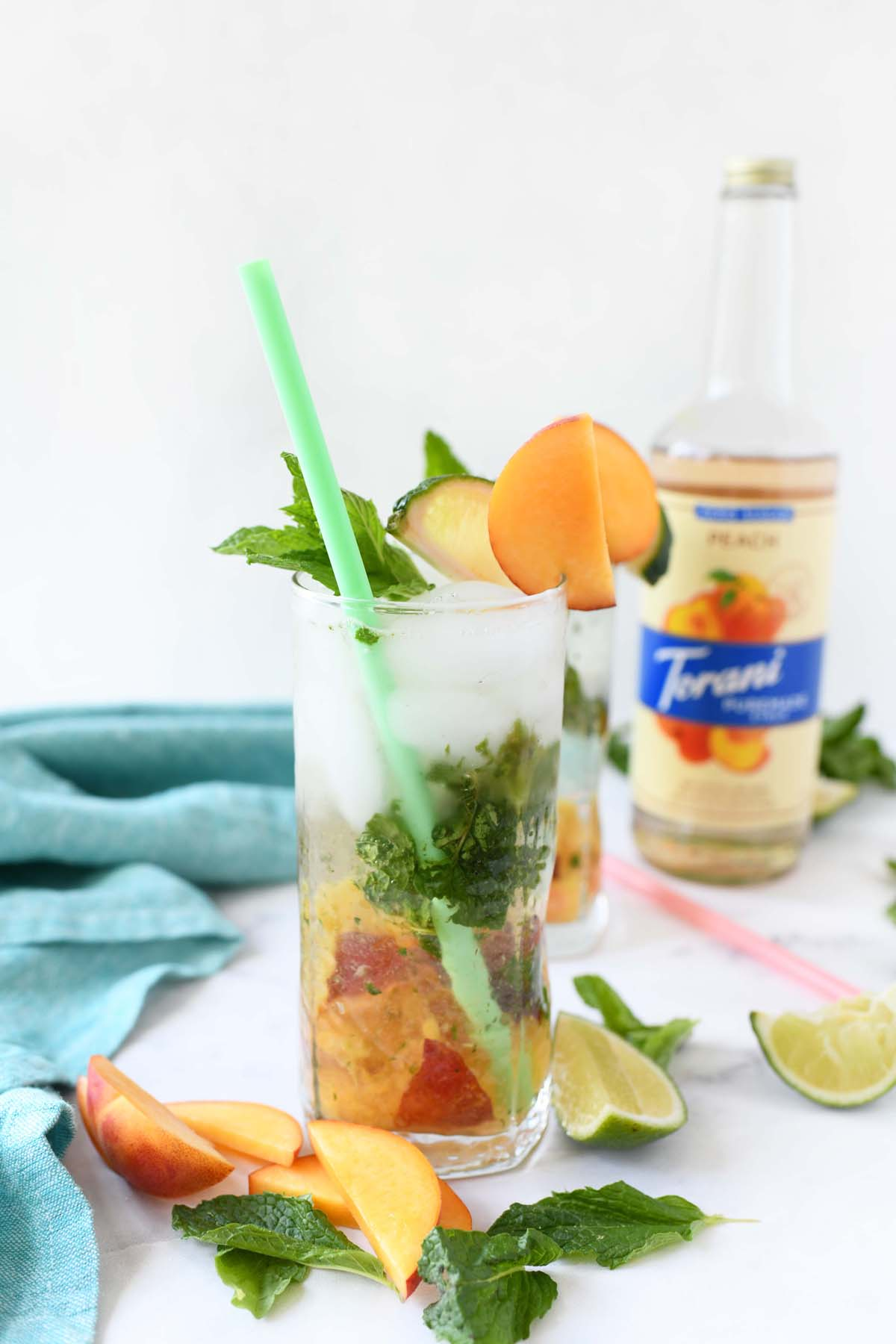 Mint Peachy Mojito with a green straw and fresh peach slices.