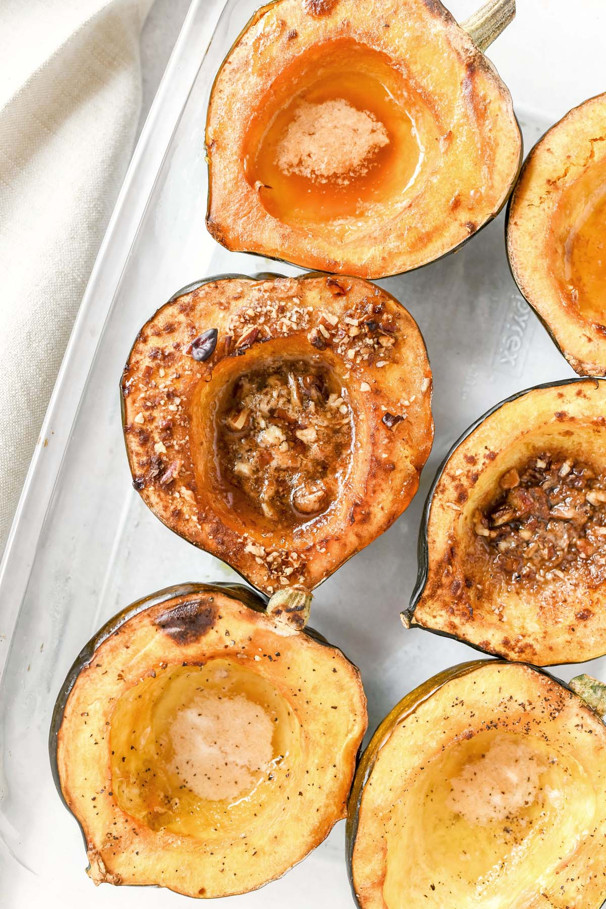 Acorn Squash roasted with butter and nuts in a clear, glass dish.