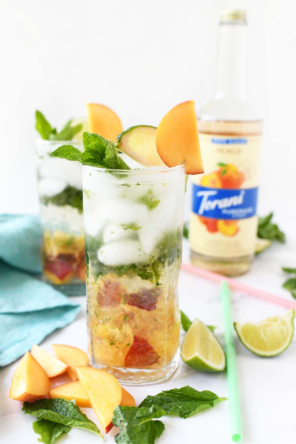 Peachy mint mojito in a tall glass.