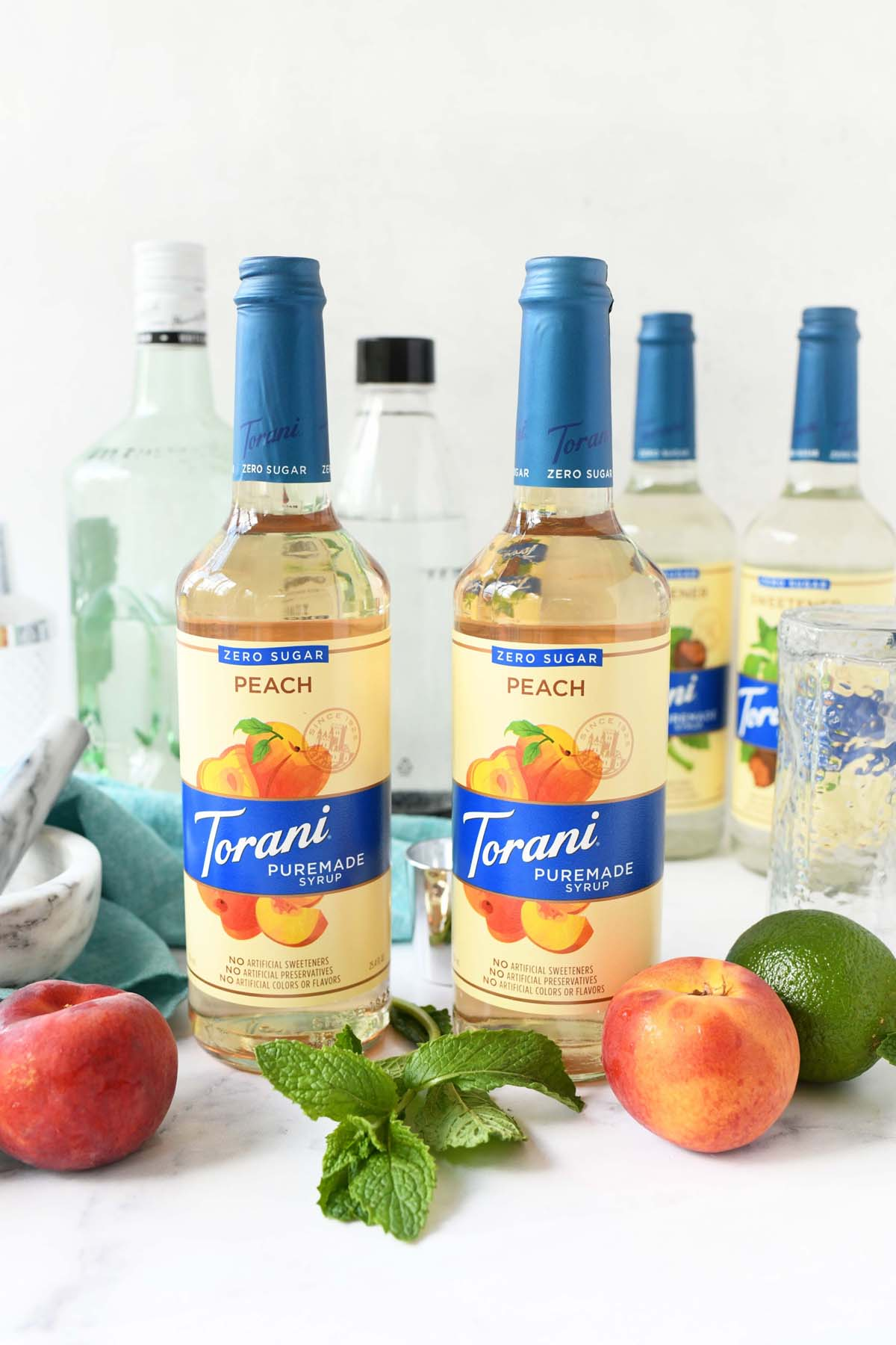 Two bottles of Torani Puremade near fresh peaches and lime.