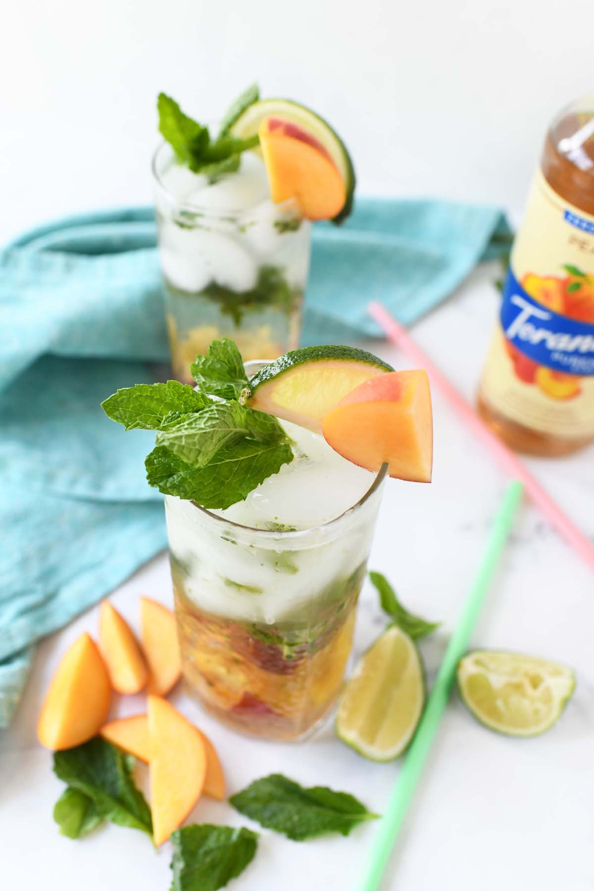 A peach mojito with bright green mint leaves on top.