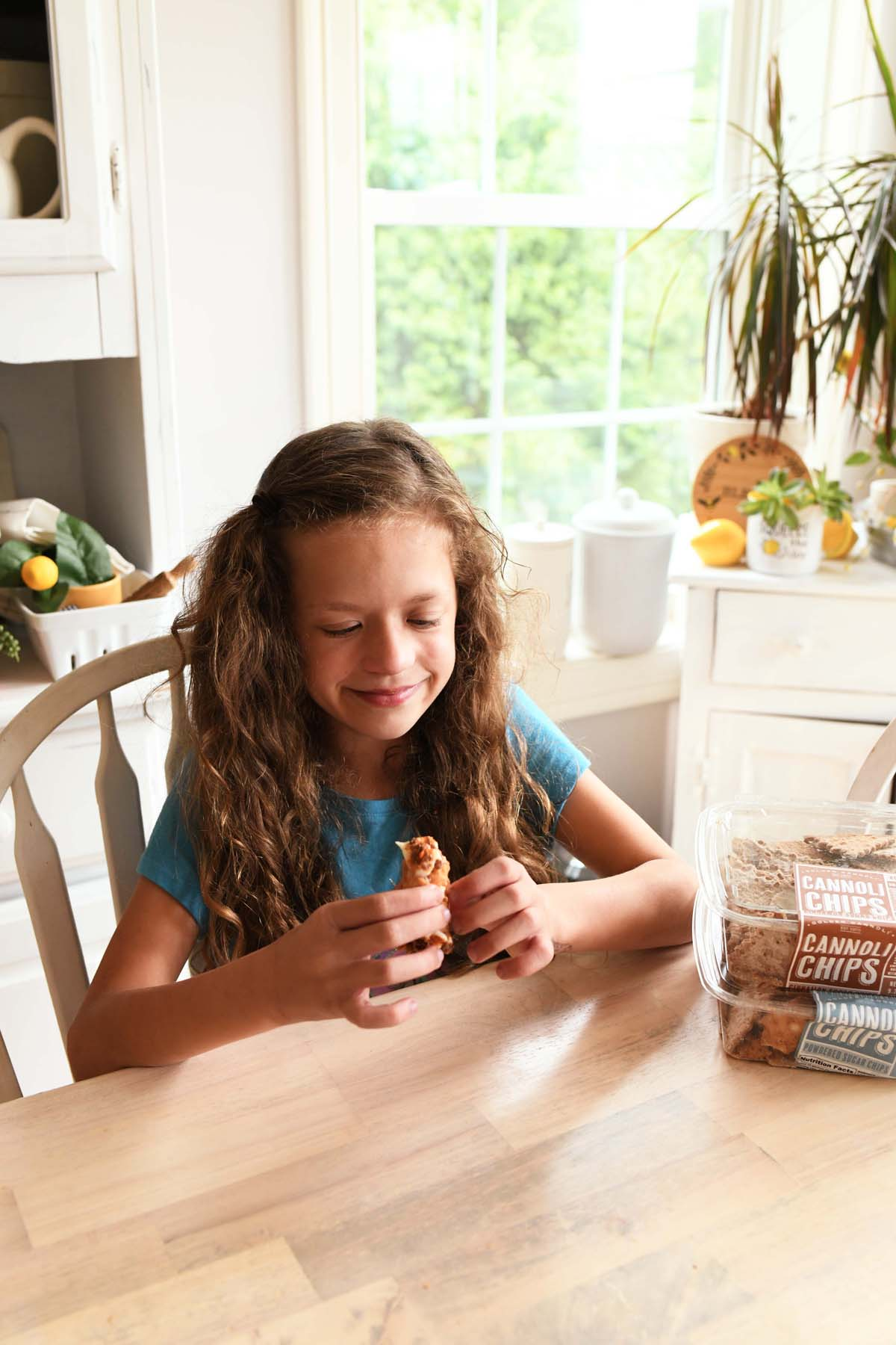 A little girl eating a cannoli.