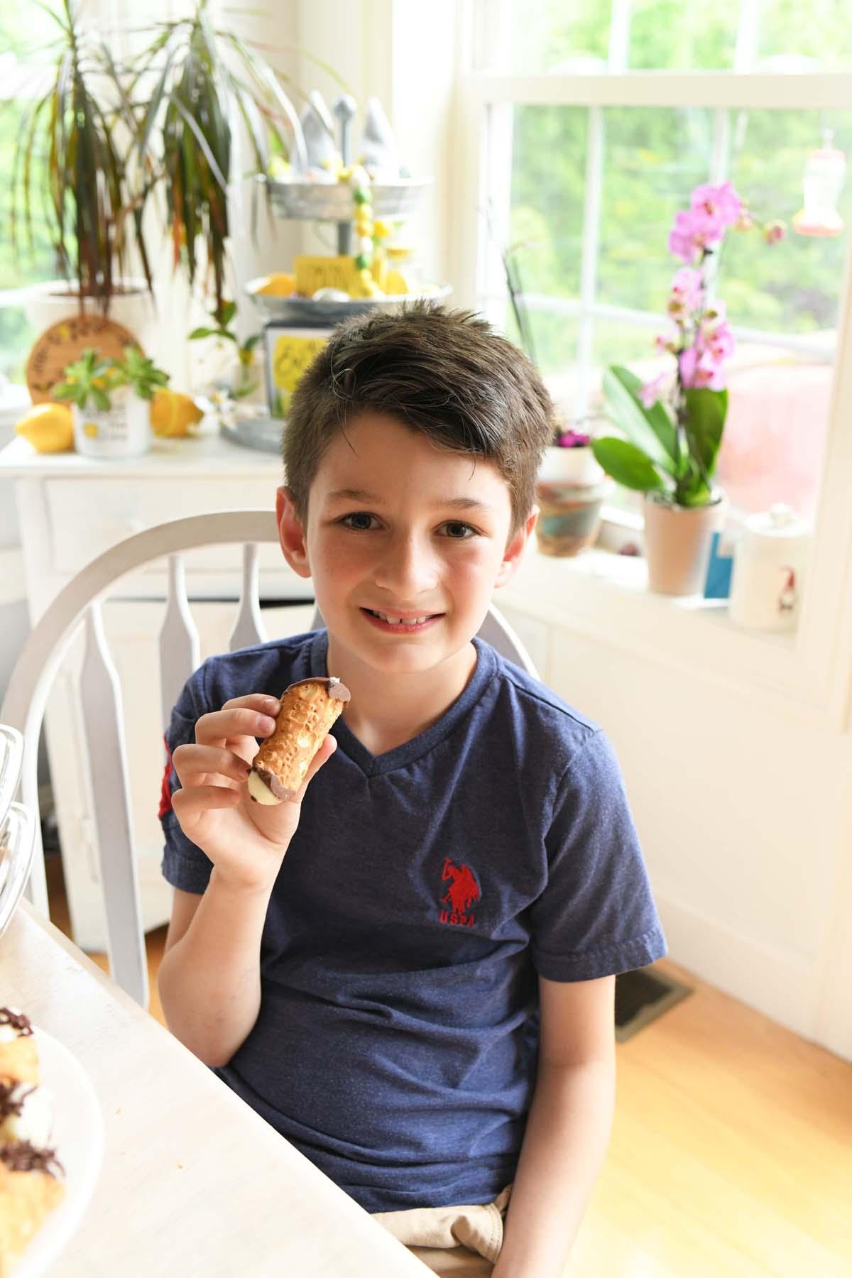 Boy eating a Golden Cannoli.