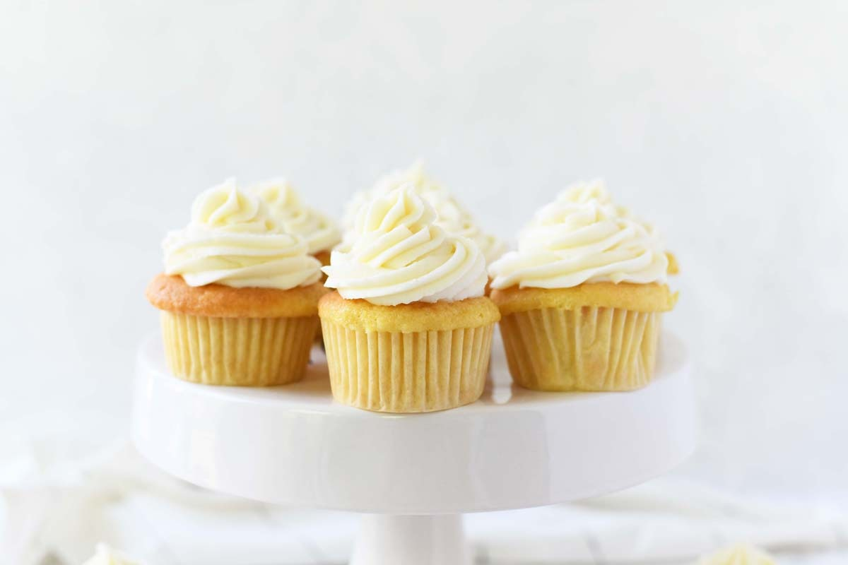 French vanilla cupcakes on a white cake stand.