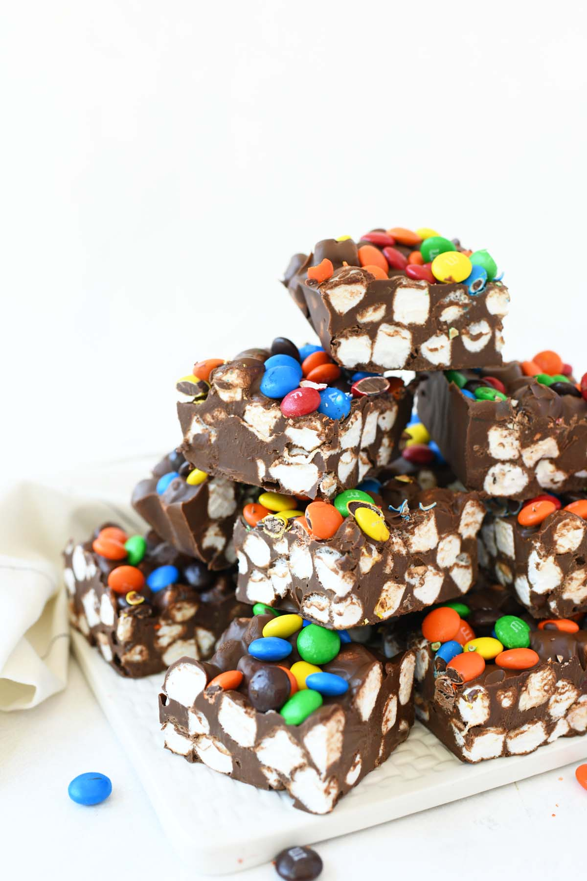 A stack of colorful Marshmallow Dream Bars on a white tray.