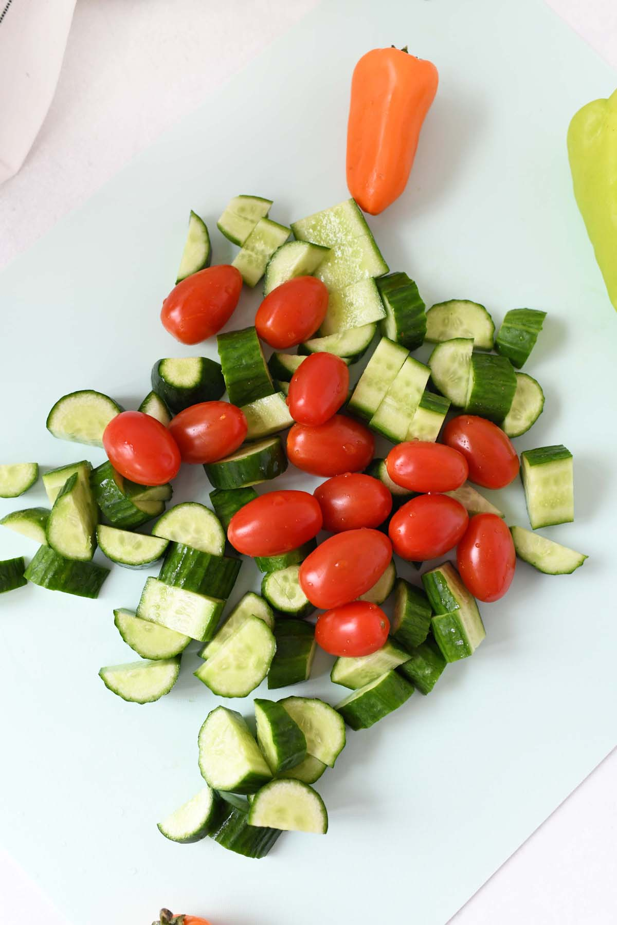 Chopped Cucumber pieces and tomatoes on a blue cutting board.