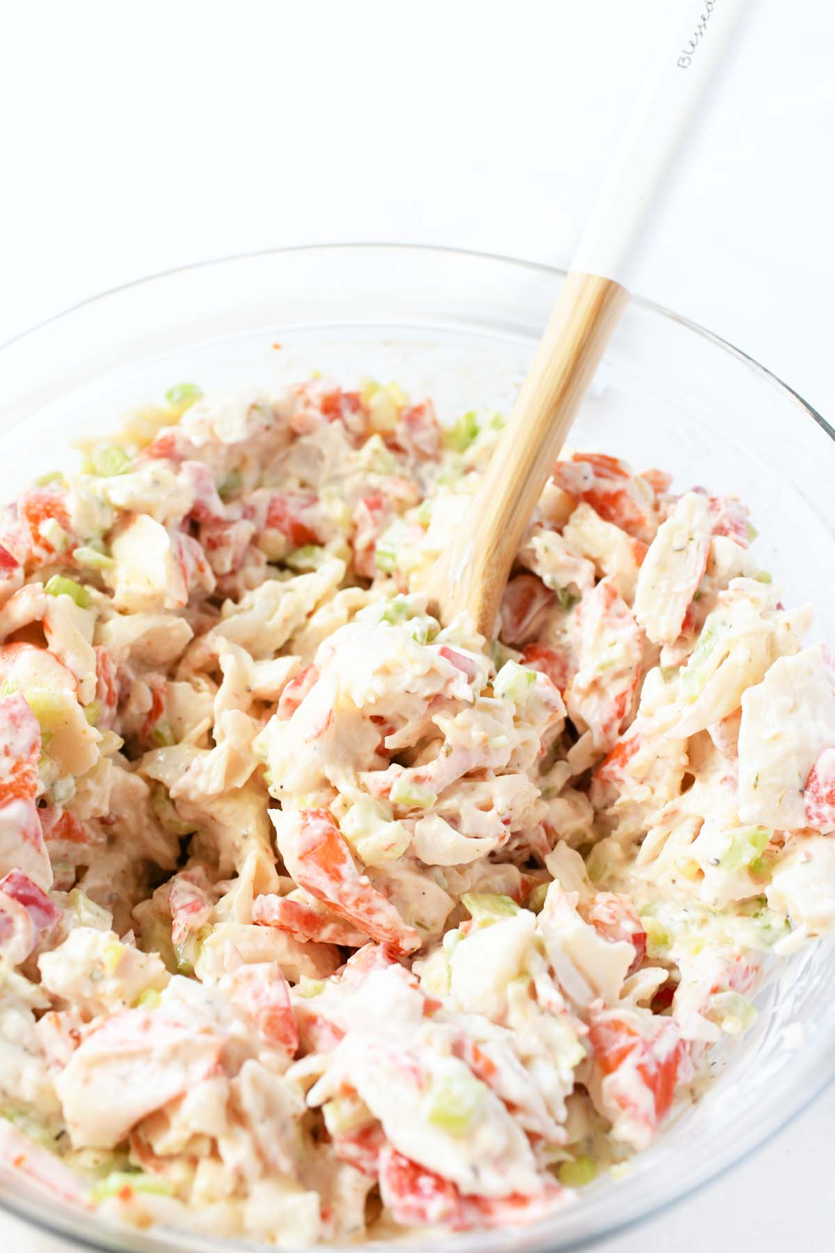 Chunky crab salad with a wooden spoon.