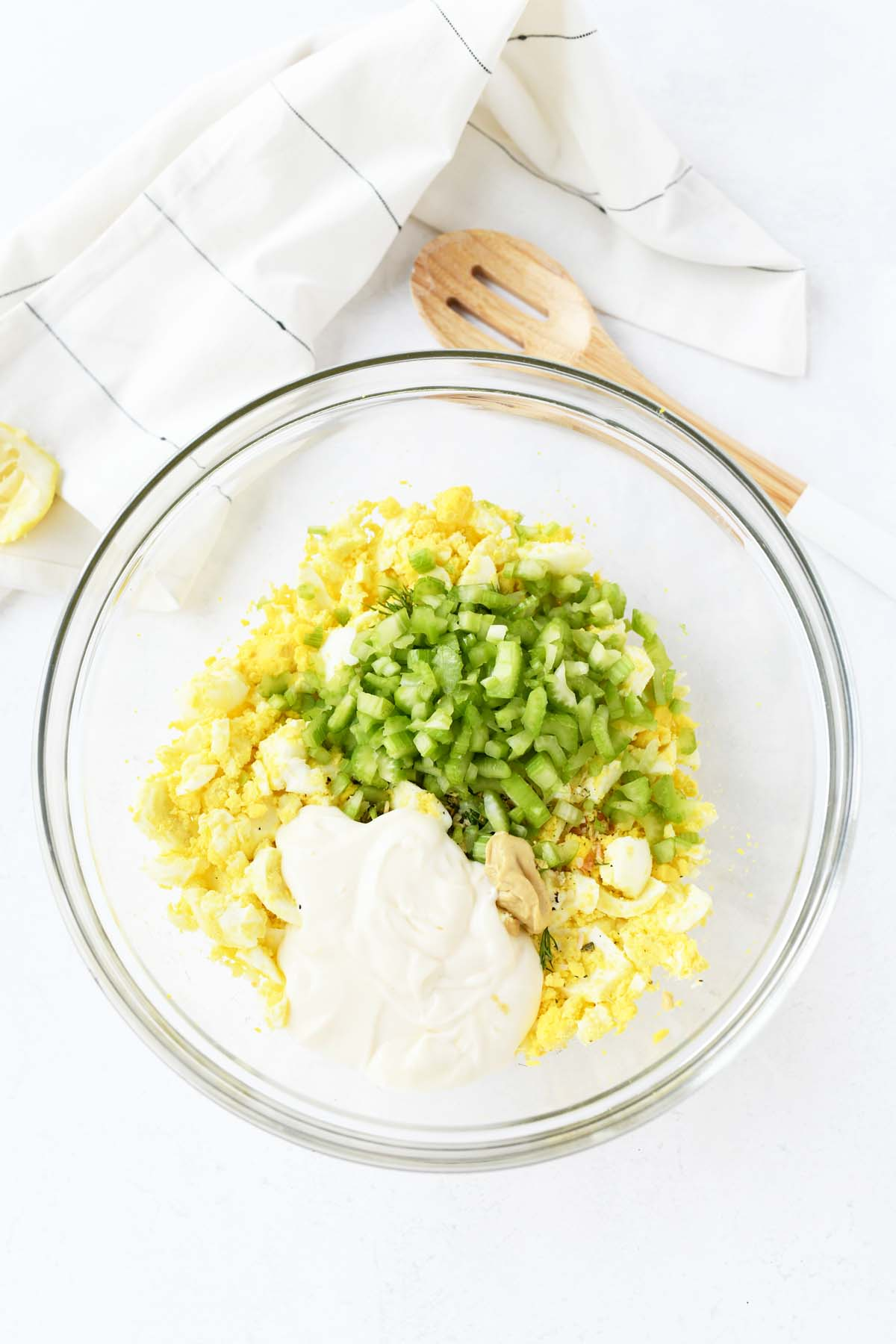 Egg salad ingredients in a bowl on a white table.