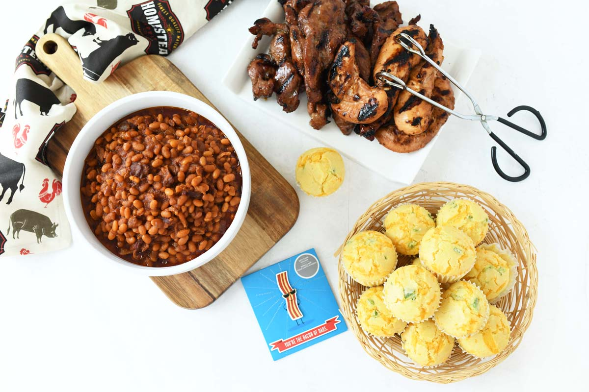 A spread of BBQ food on a white table.