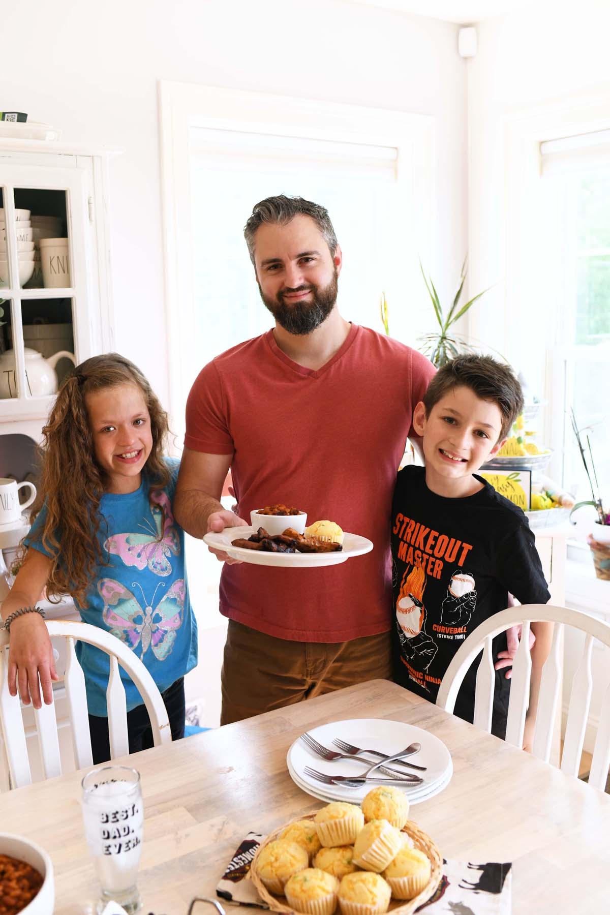 A man with a son and daughter smiling with food.