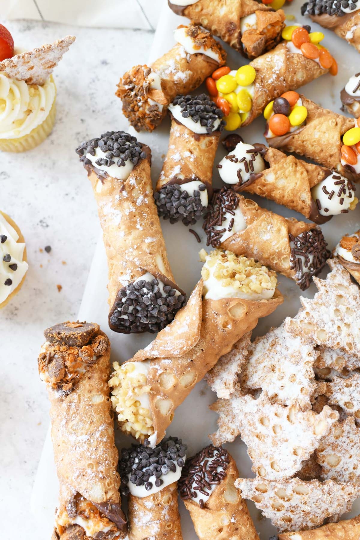 Golden Cannoli filled pastries on a marble serving platter.