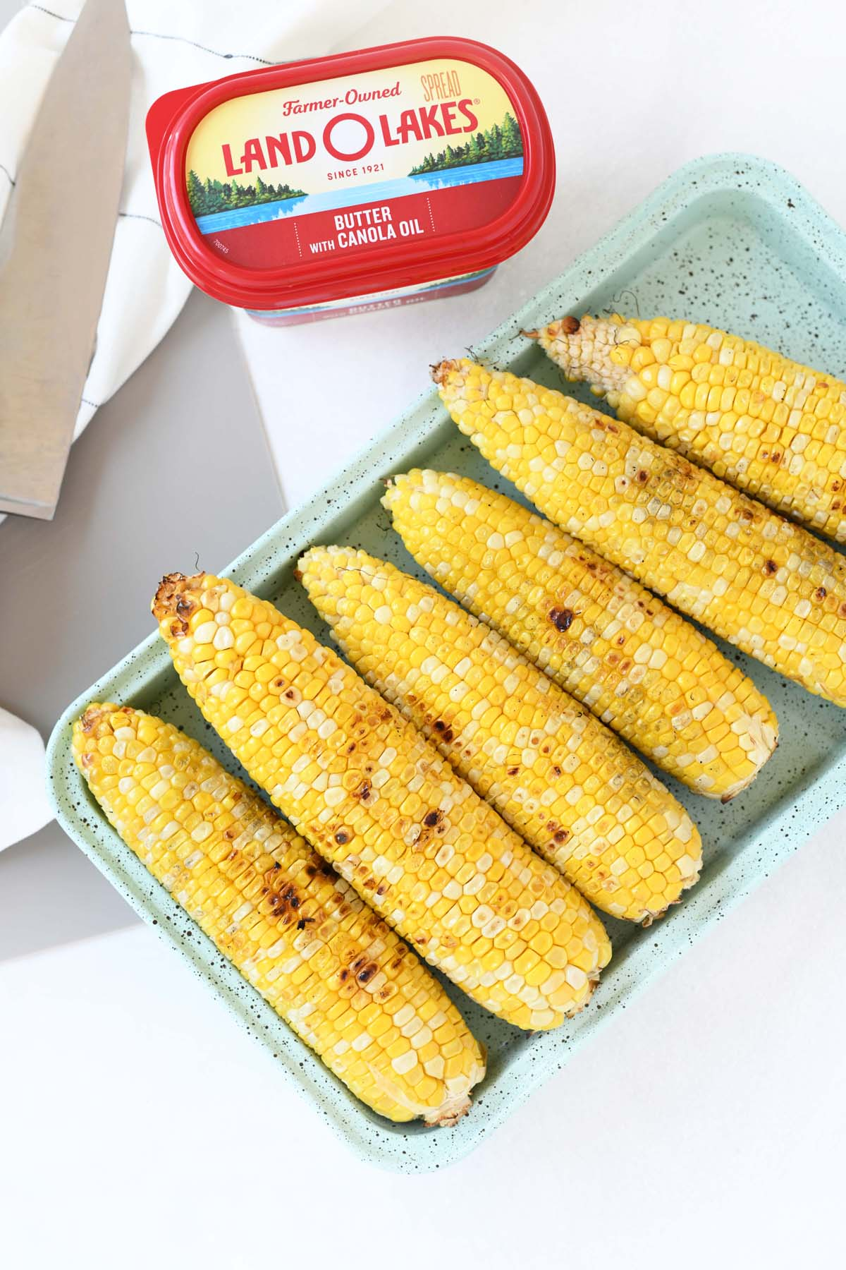 Grilled Corn on the Cob in a blue dish with Land O Lakes Butter nearby.