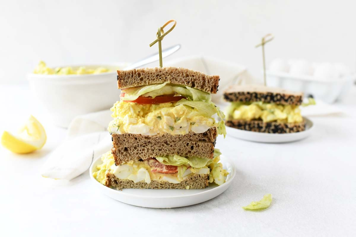 Keto egg salad sandwich stacked on a white table.