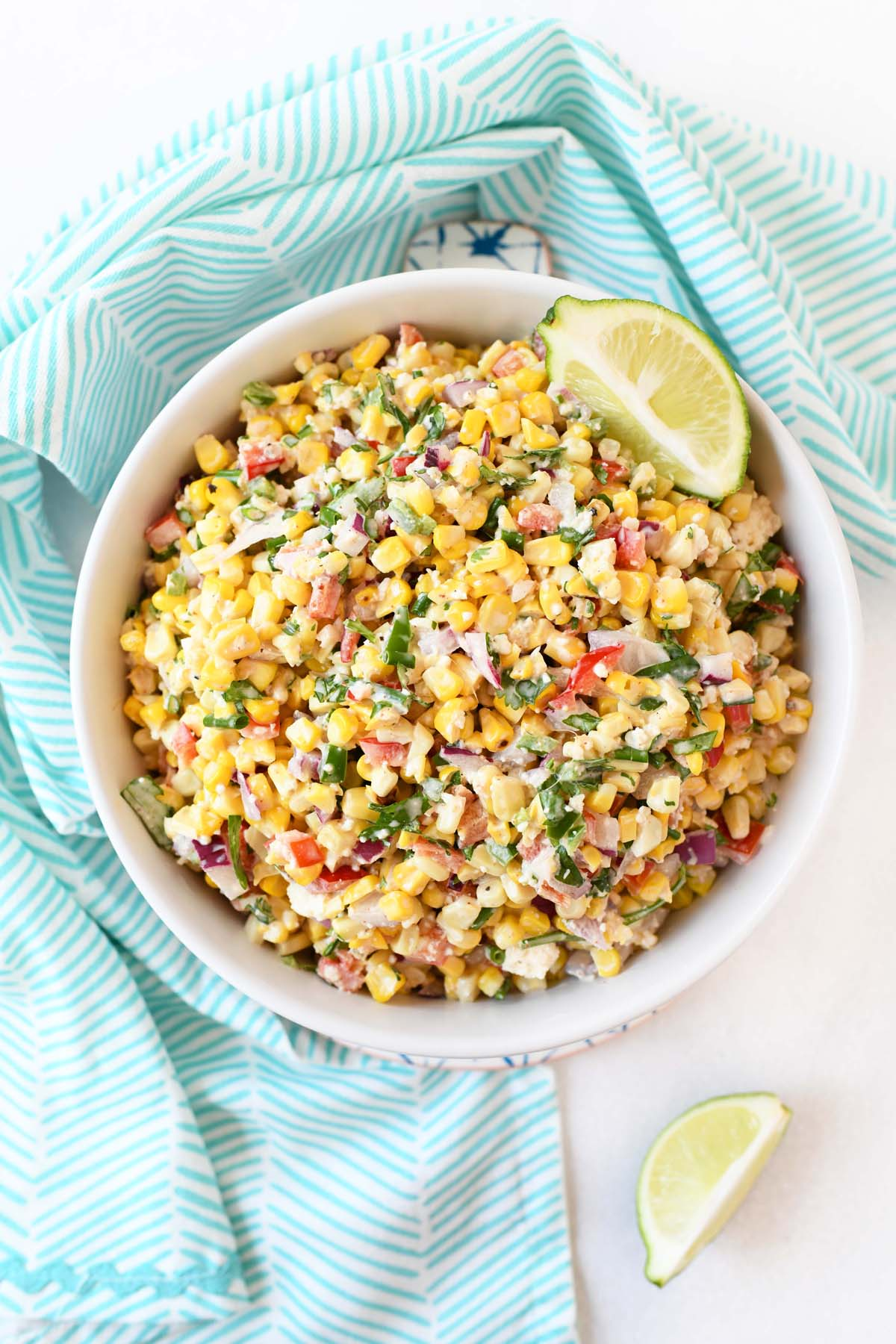 Mexican Corn Salad with cotija cheese in a white bowl with a blue napkin.