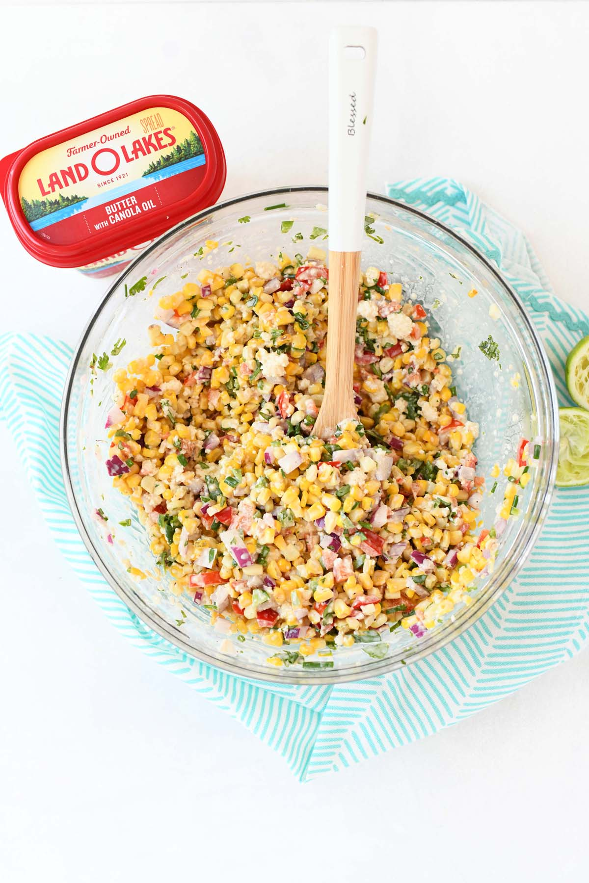 Mexican Street Corn Salad near butter in a glass bowl with a spoon.