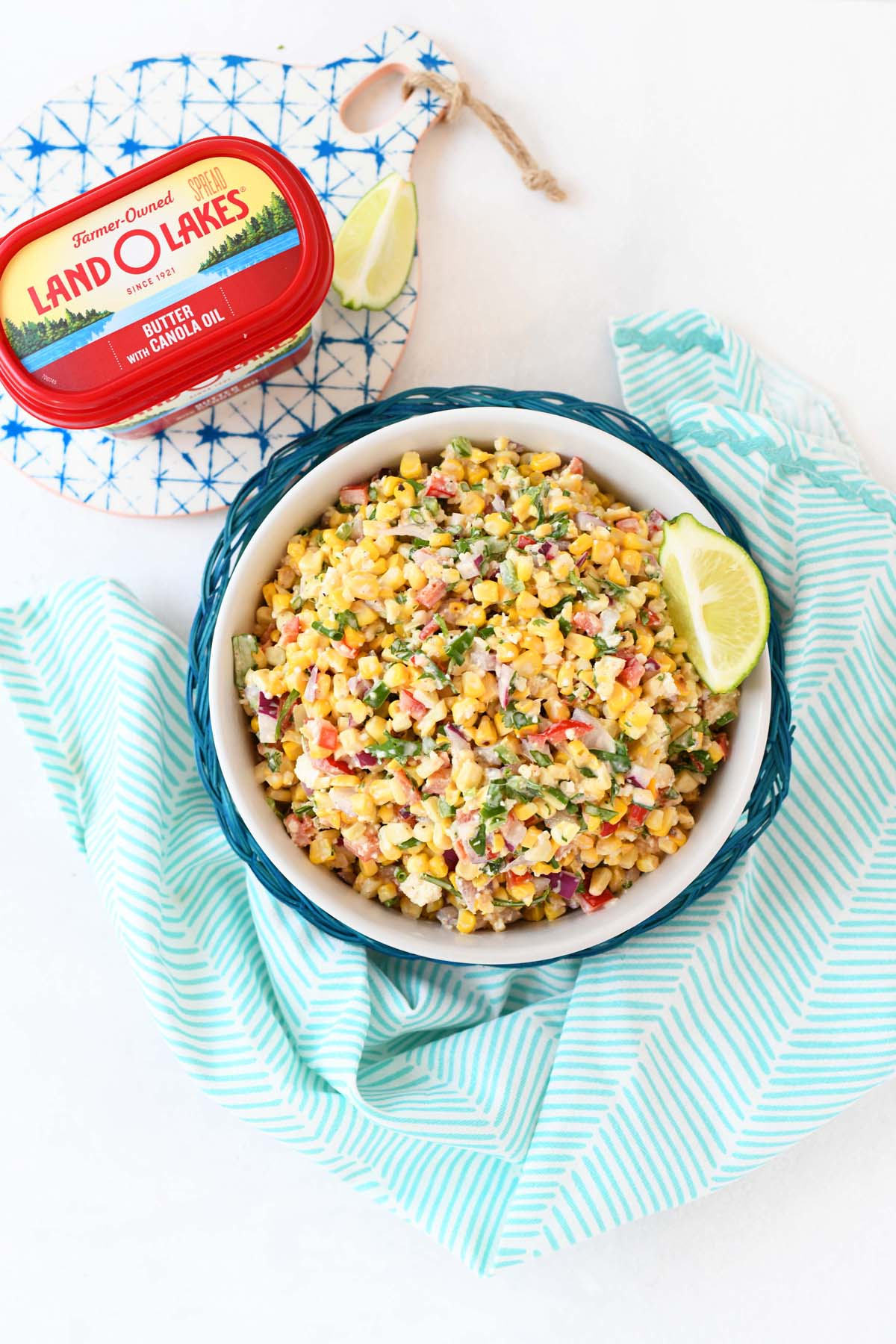 Mexican Street Corn salad in a glass bowl near a blue napkin and butter tub.
