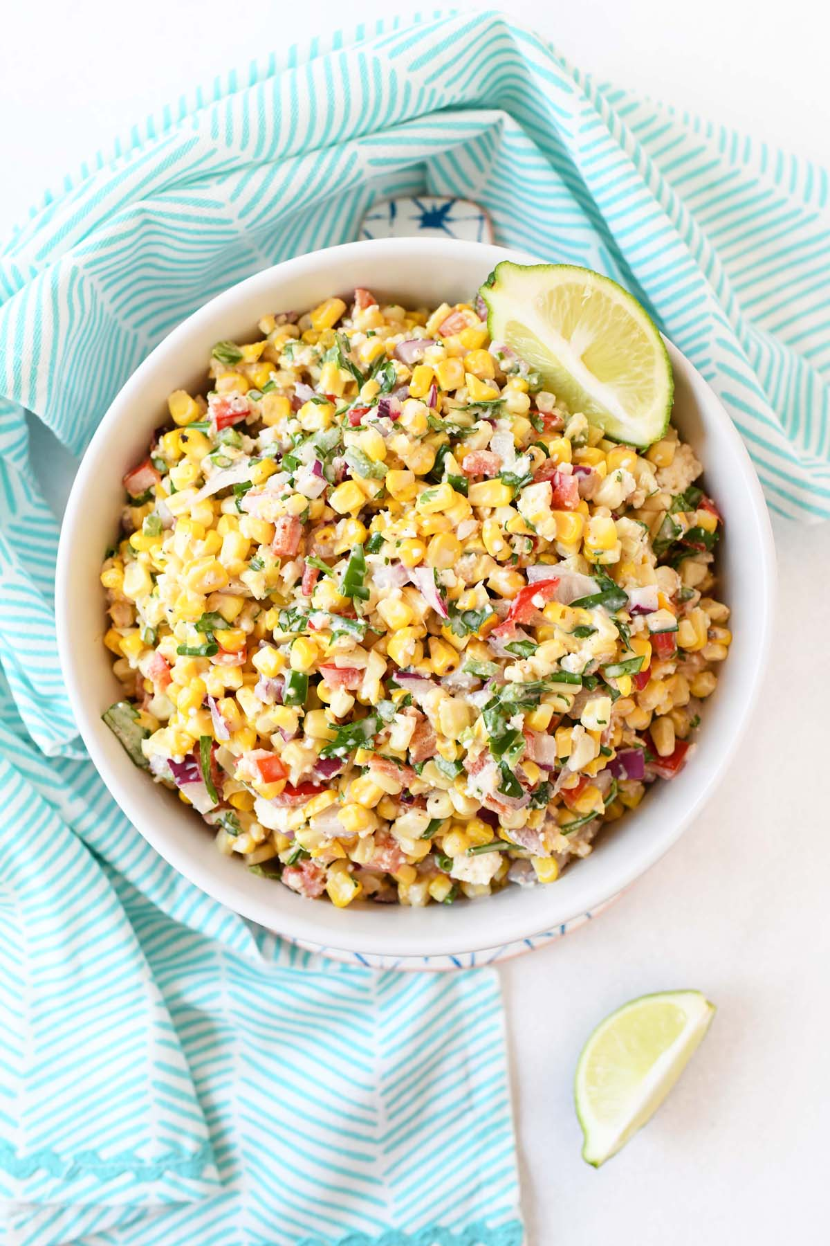 Mexican street Corn Salad with lime  wedges in a white bowl.