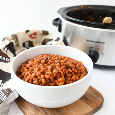 Slow cooker baked beans in a white bowl.