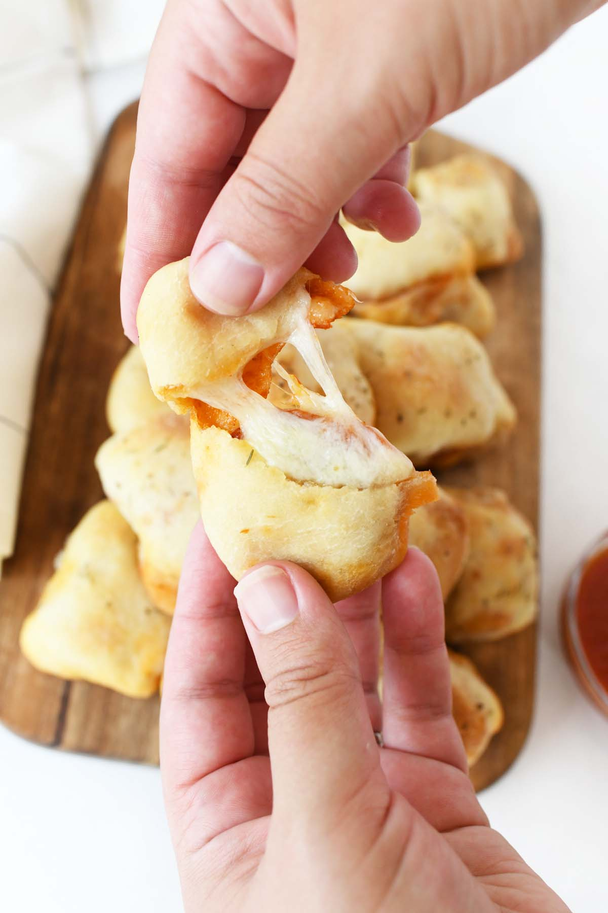 A hand stretching a cheesy pepperoni pizza roll.