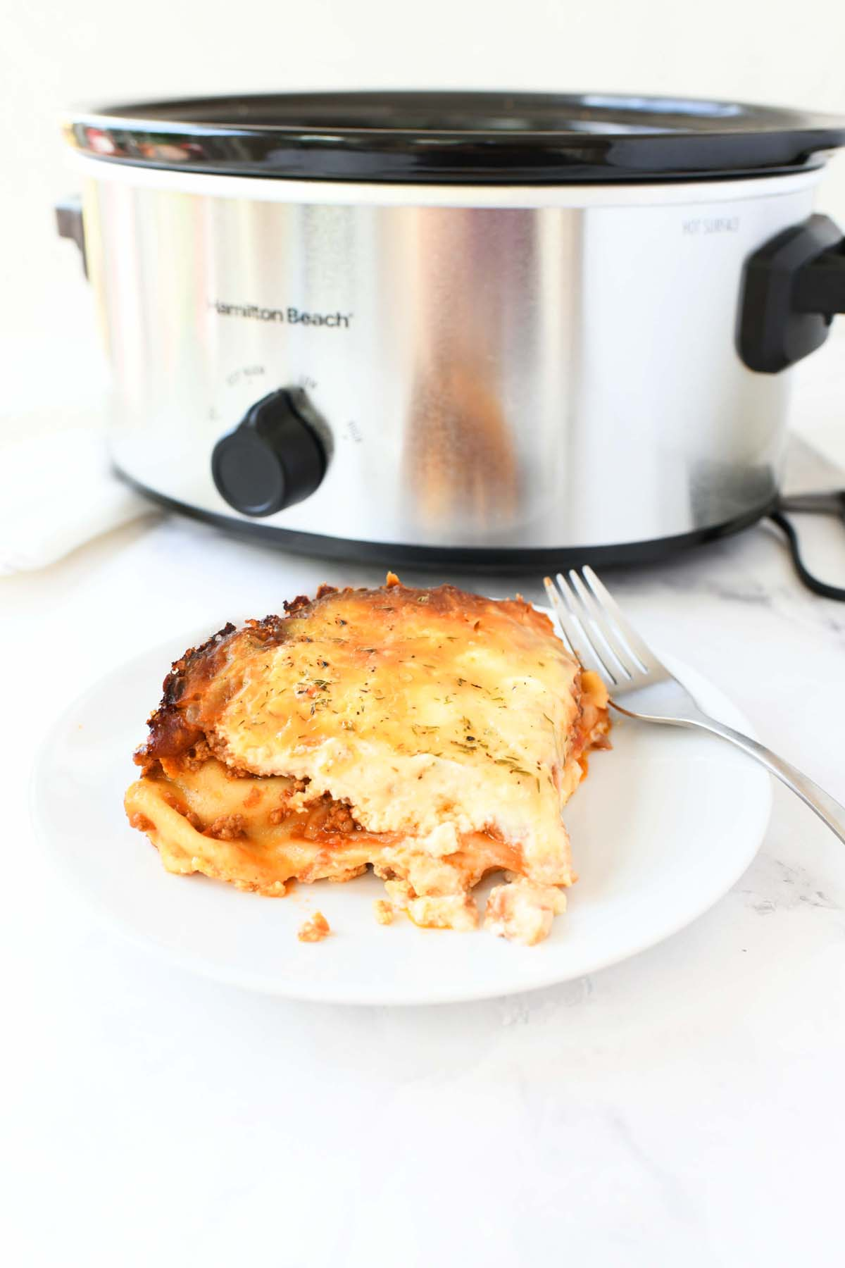A slice of slow cooker lasagna on a white plate.