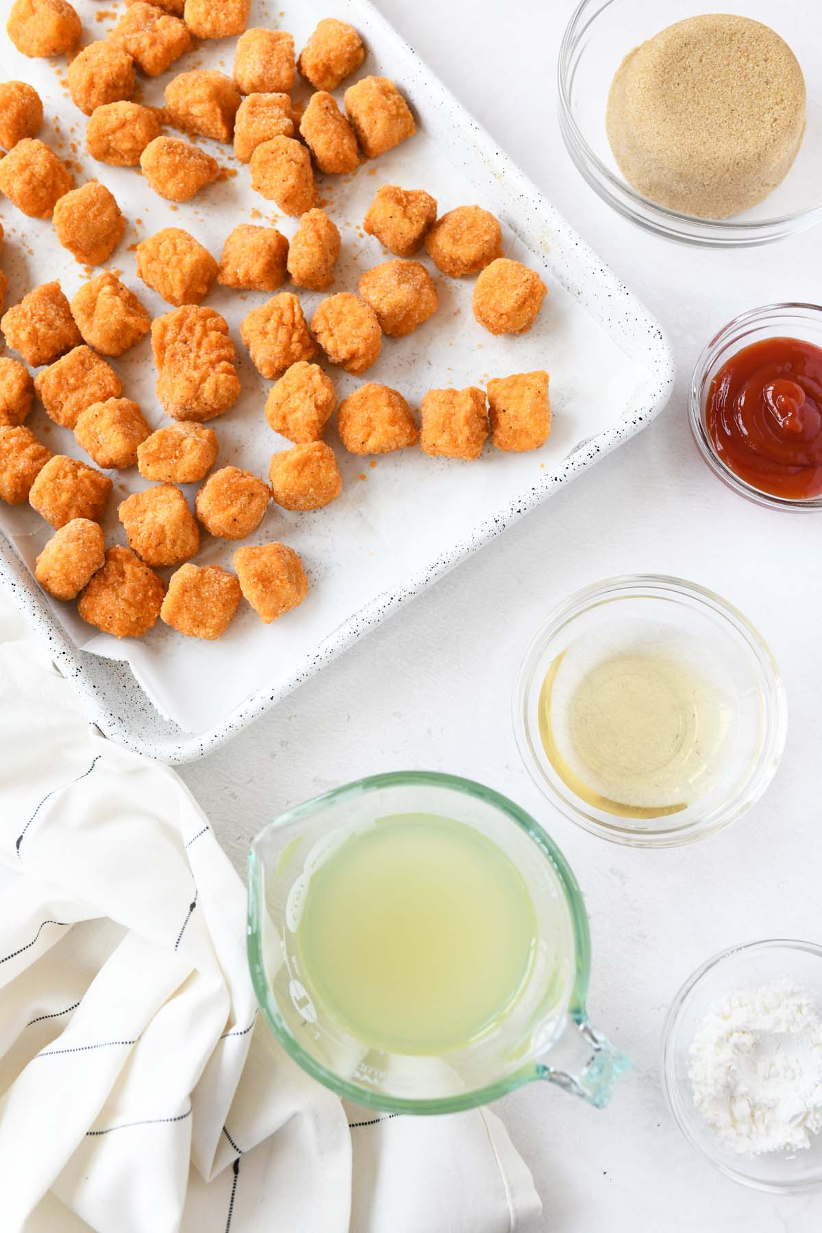 Popcorn chicken on a baking sheet with ingredients nearby.