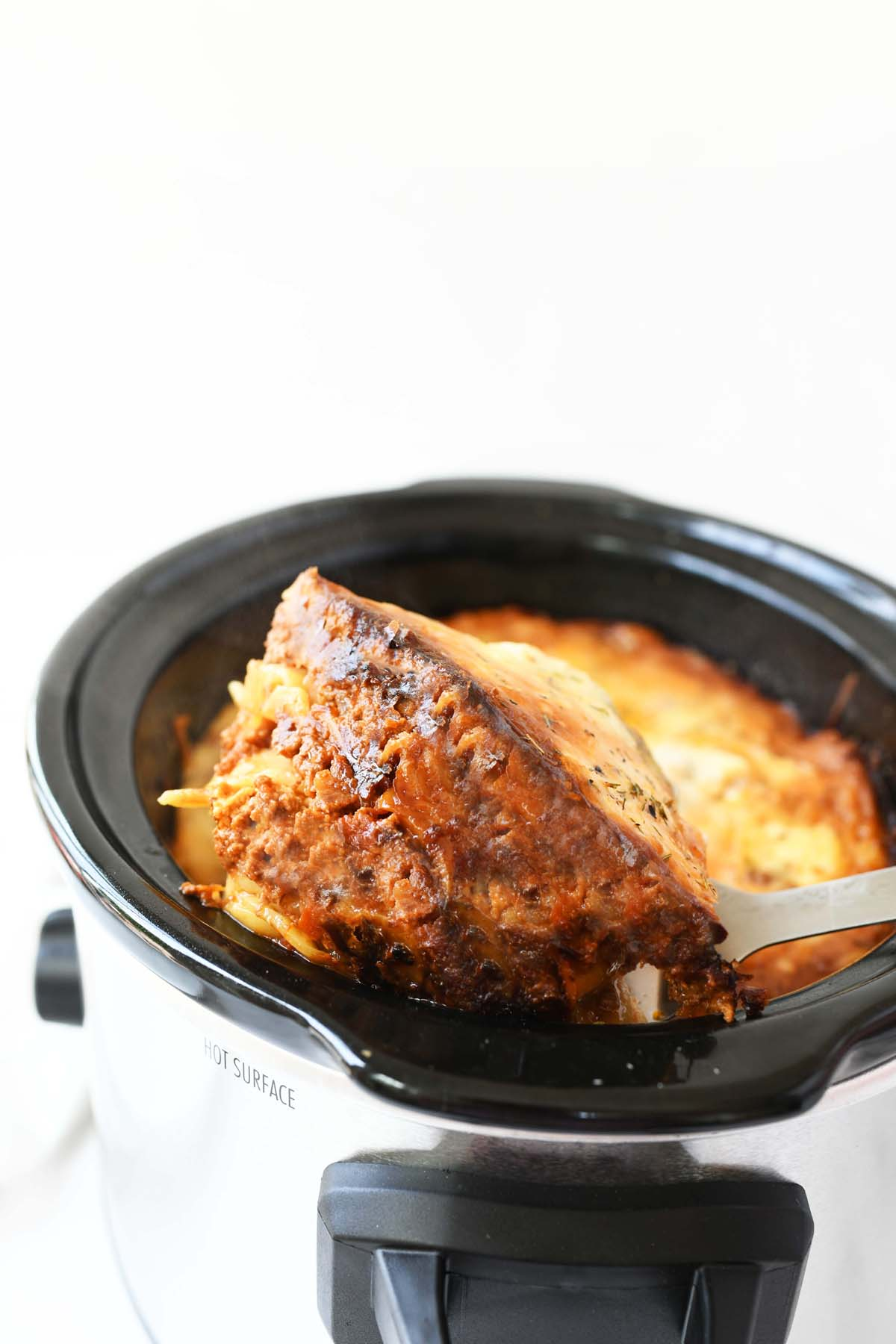 Slow Cooker Lasagna Slice coming out of a pan.
