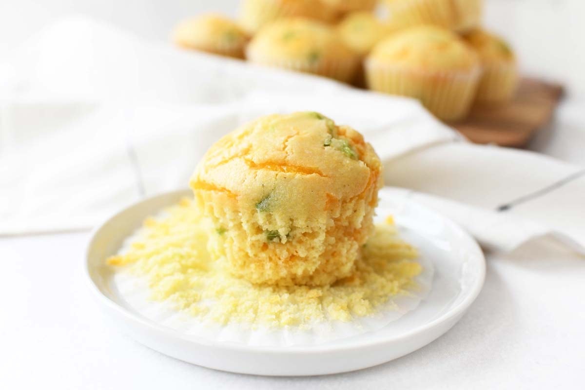 A jalapeno cheddar corn muffin on a white plate.