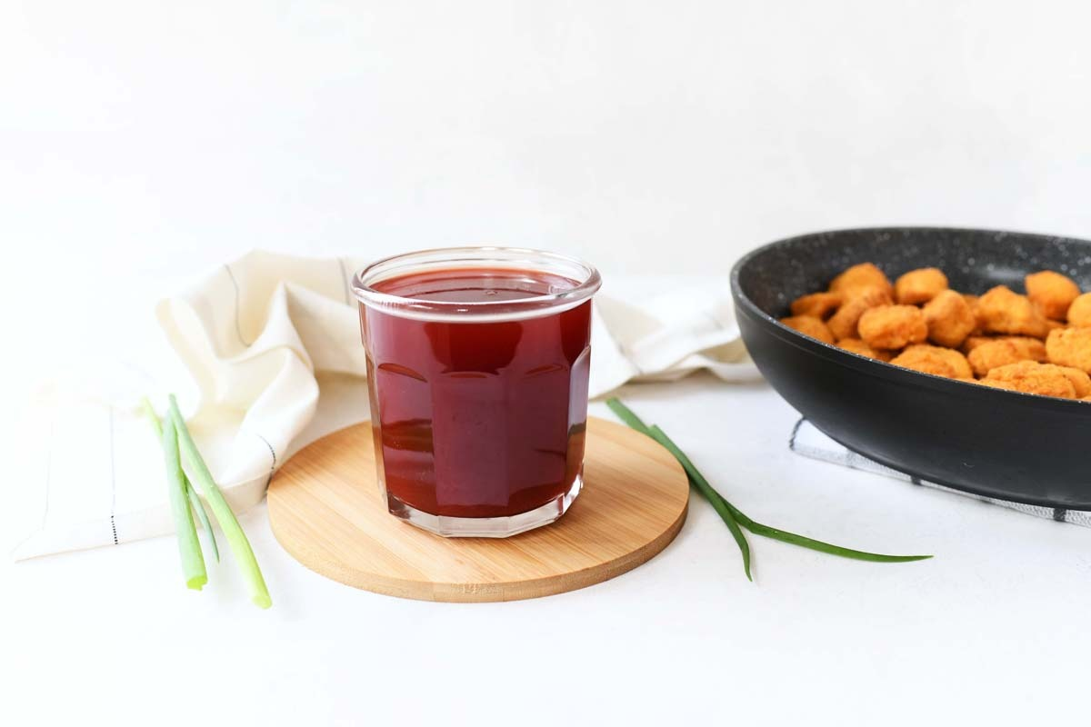 A glass jar of Sweet and Sour Sauce on a white table.