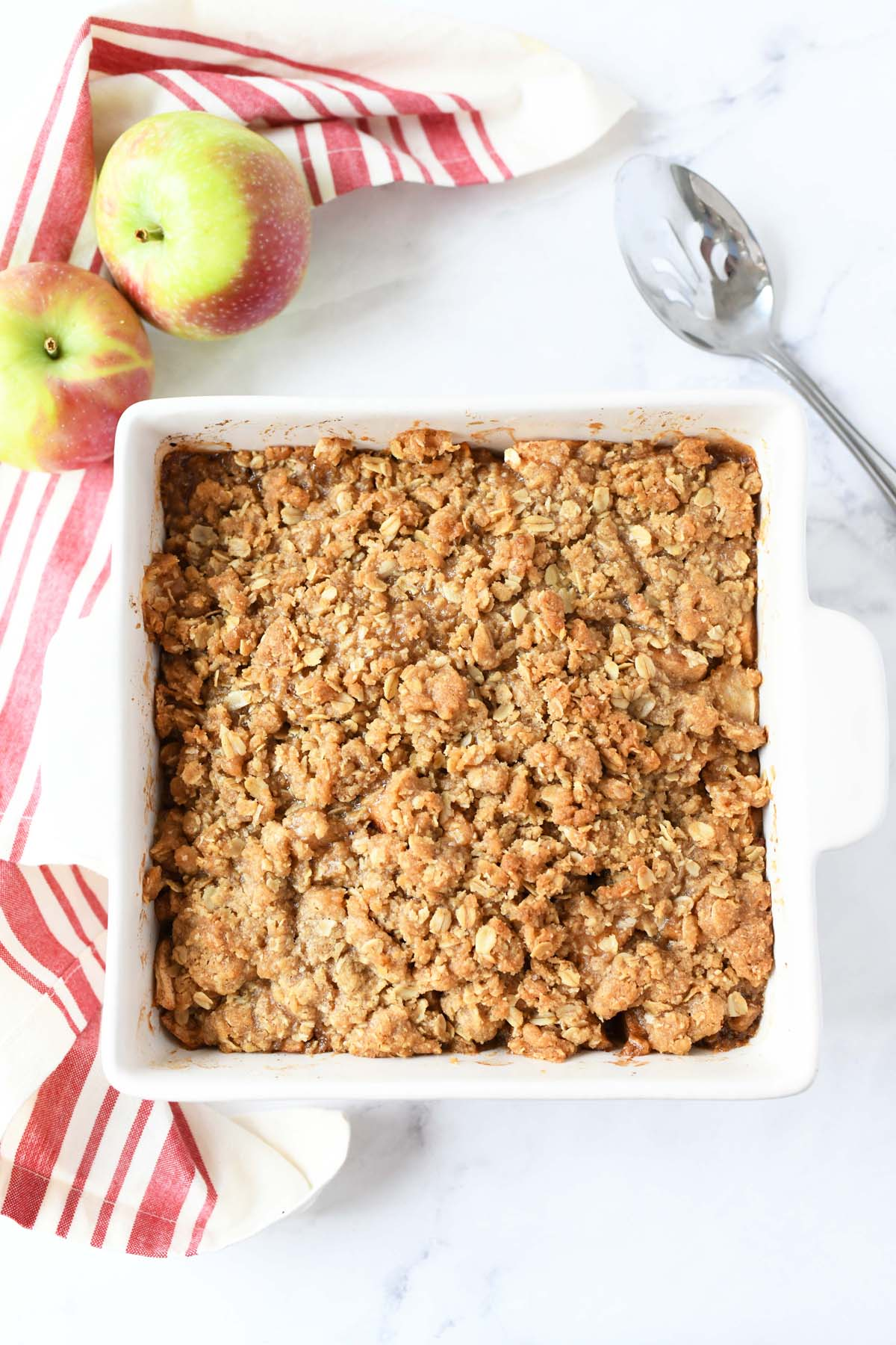 Baked apple crisp in a small white rectangle pan.