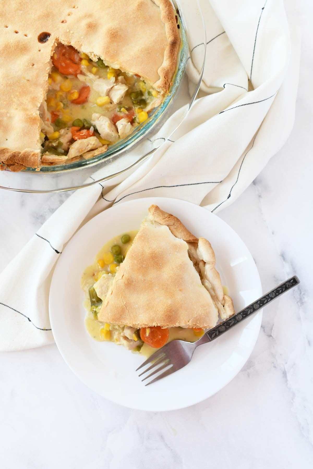A slice of chicken pot pie on a small white dish.