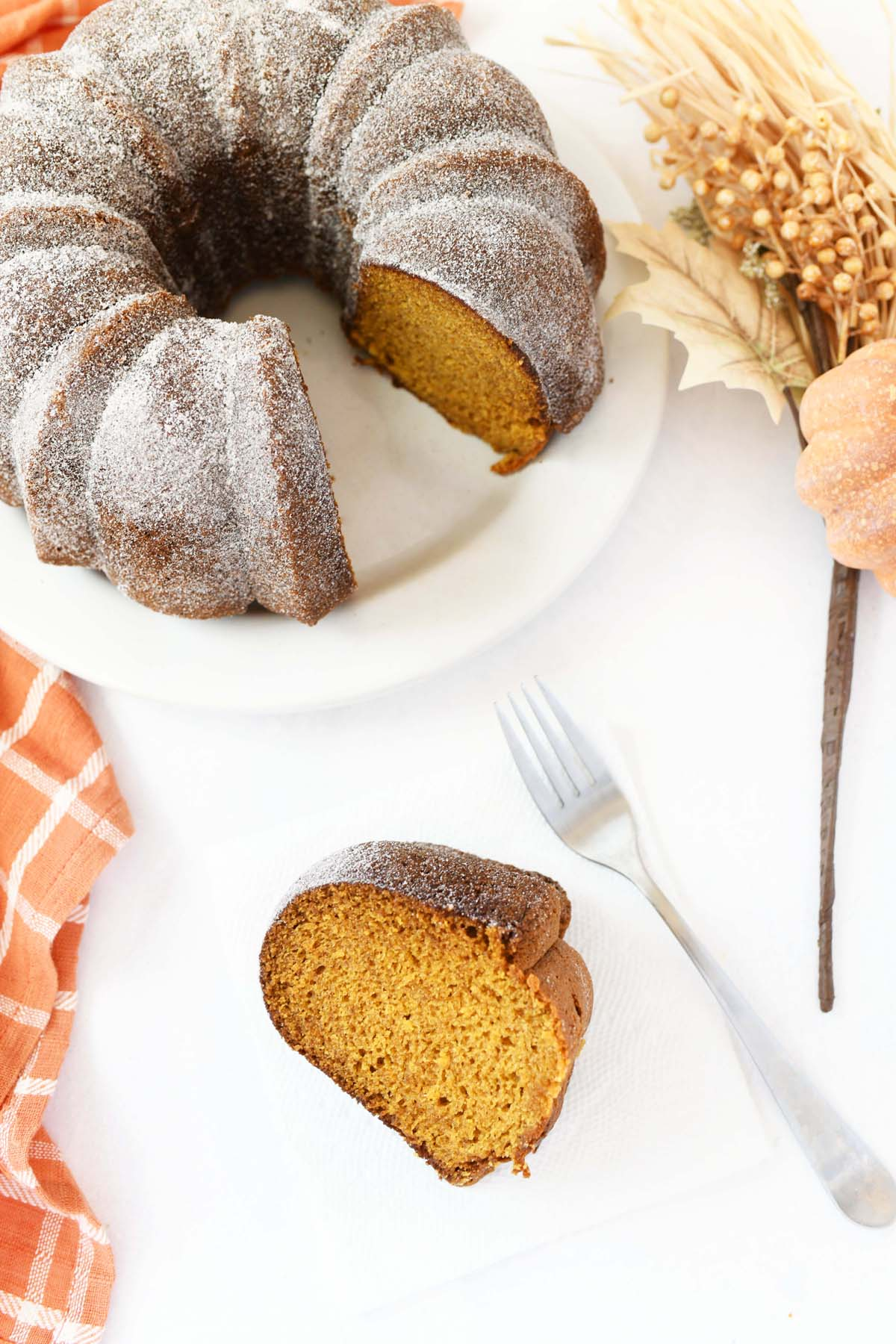 Cinnamon and Sugar Pumpkin Cake on a white plate with a silver fork.