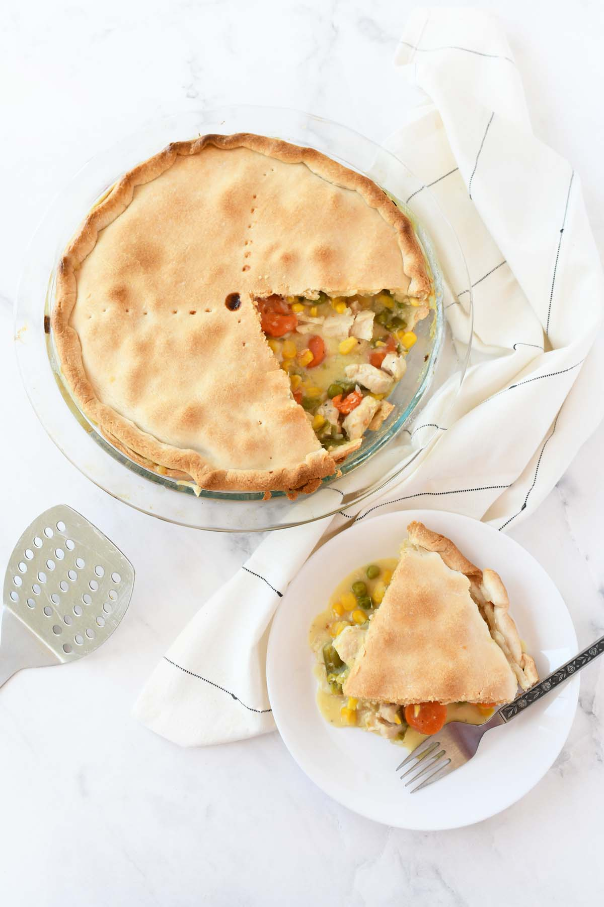 A delicious pie slice on a white dish with a fork.