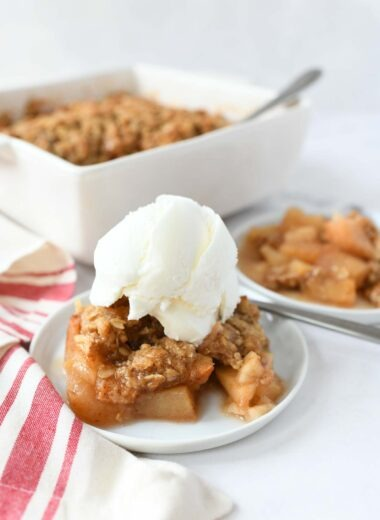 A small bowl of apple crisp with a dollop of vanilla ice cream on top.